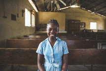 Smiling girl sitting in a church pew.