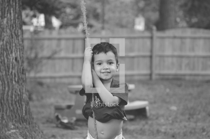 a toddler hanging onto a rope