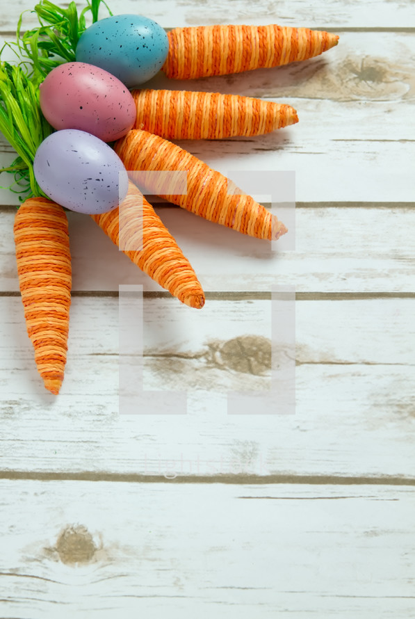 Easter eggs and carrots on wood background