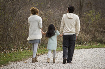 Family walking on a trail outside, holding hands.