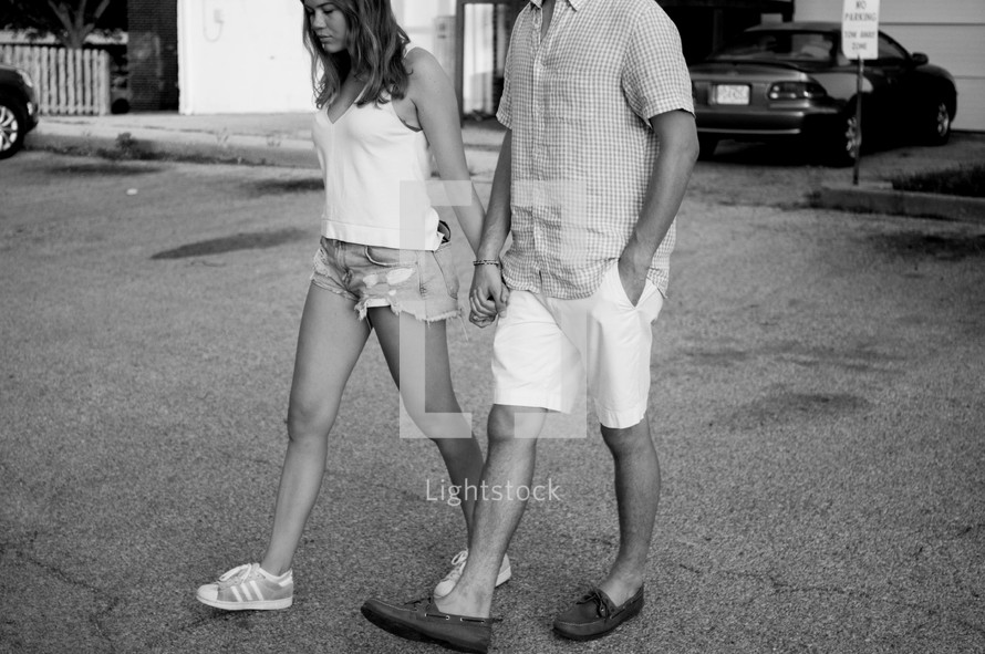 a couple in shorts walking holding hands