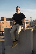 a young man sitting on a concrete wall on the roof of a building