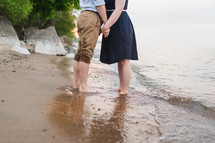 a couple standing on a beach holding hands