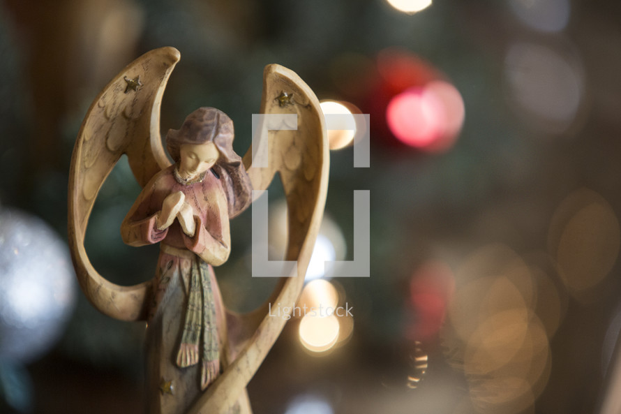 A Christmas background with a wooden angel figurine.