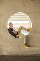 a teenage boy sitting in a circular window