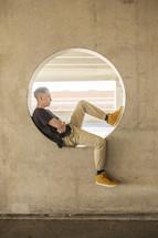 a teenage boy sitting in a circular window