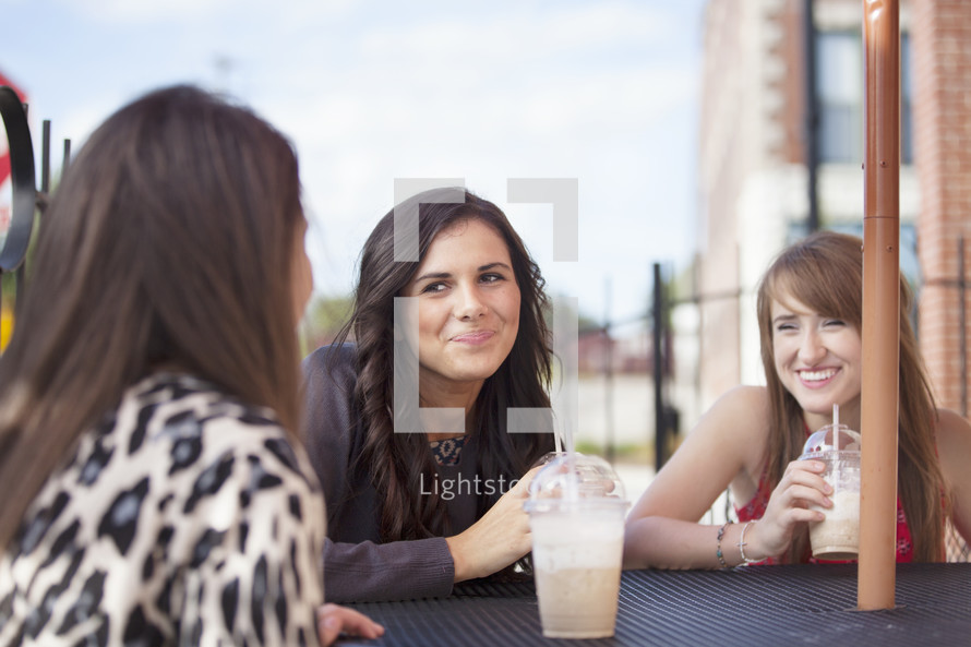friends sitting at a table drinking iced coffees