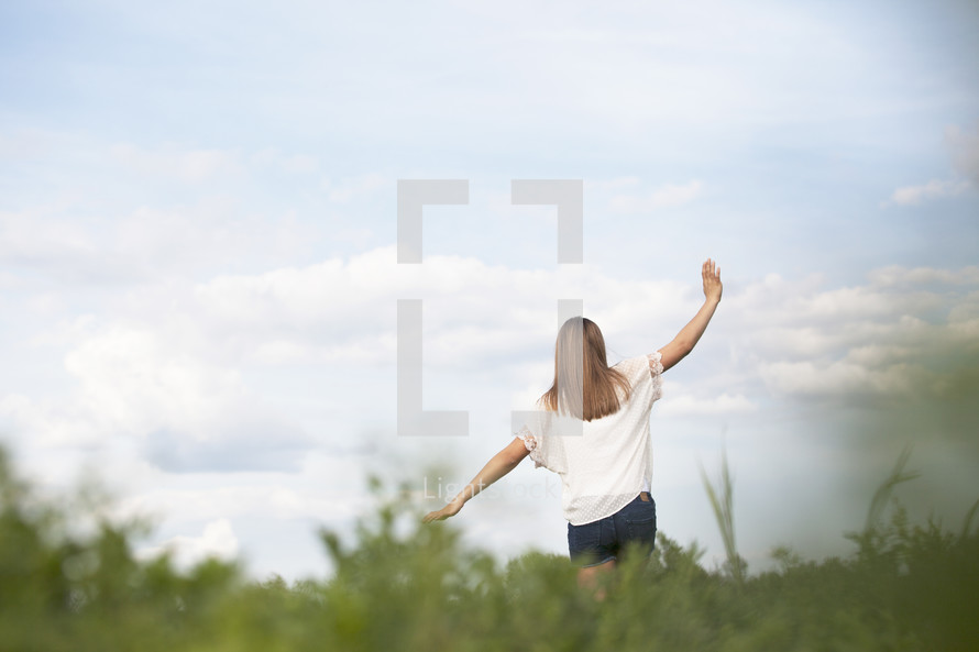 Woman walking through a field outdoors with arms extened.