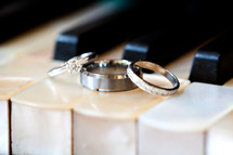 wedding bands and engagement rings on piano keys