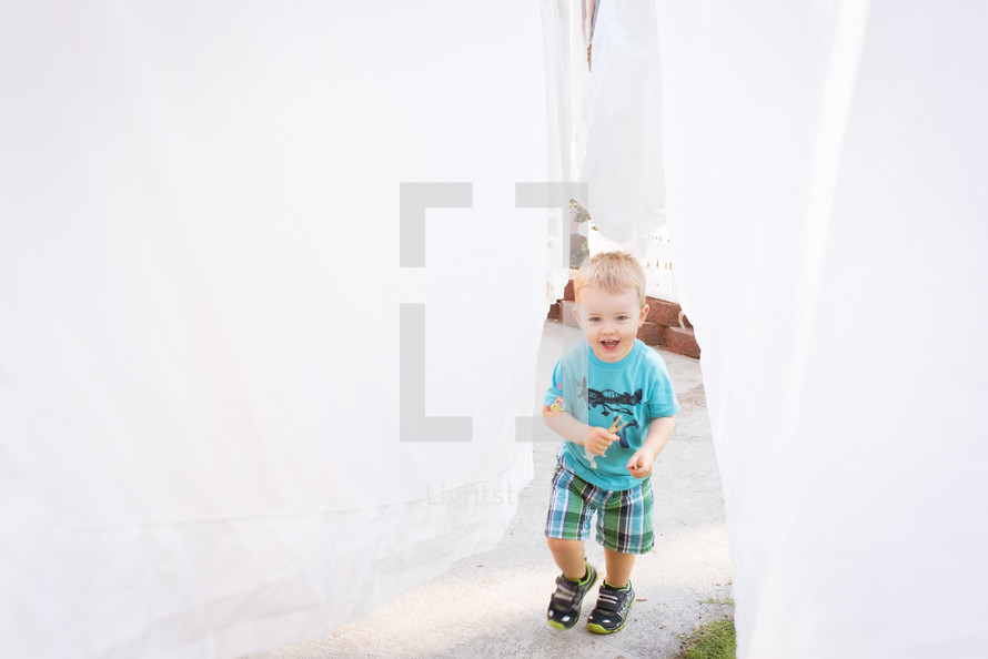 a toddler walking under hanging sheets