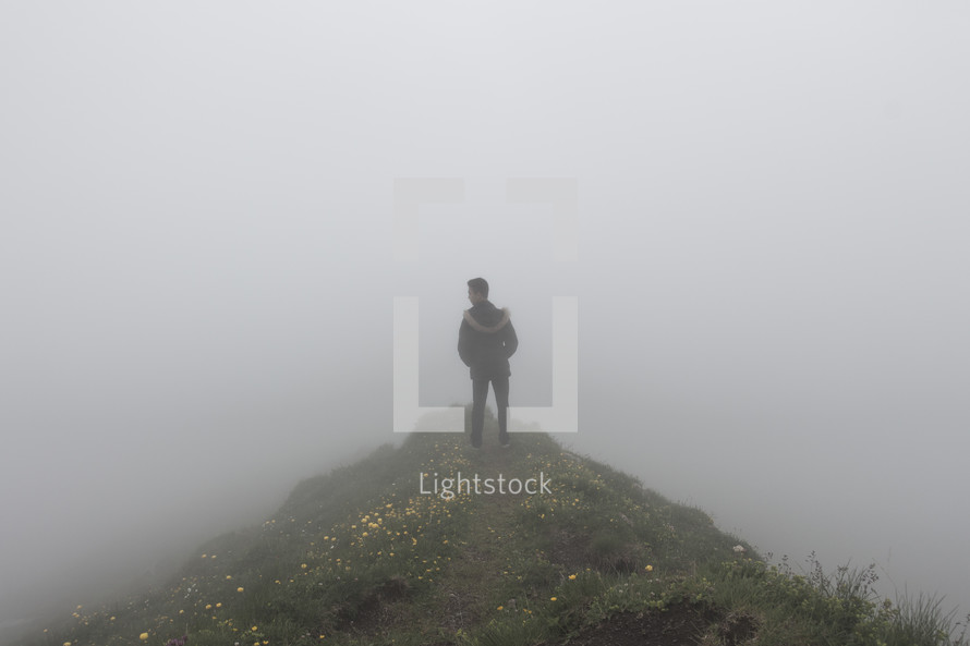 a boy standing on a hill in the fog