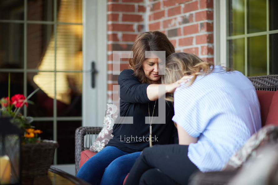 two women holding hands praying on a front porch