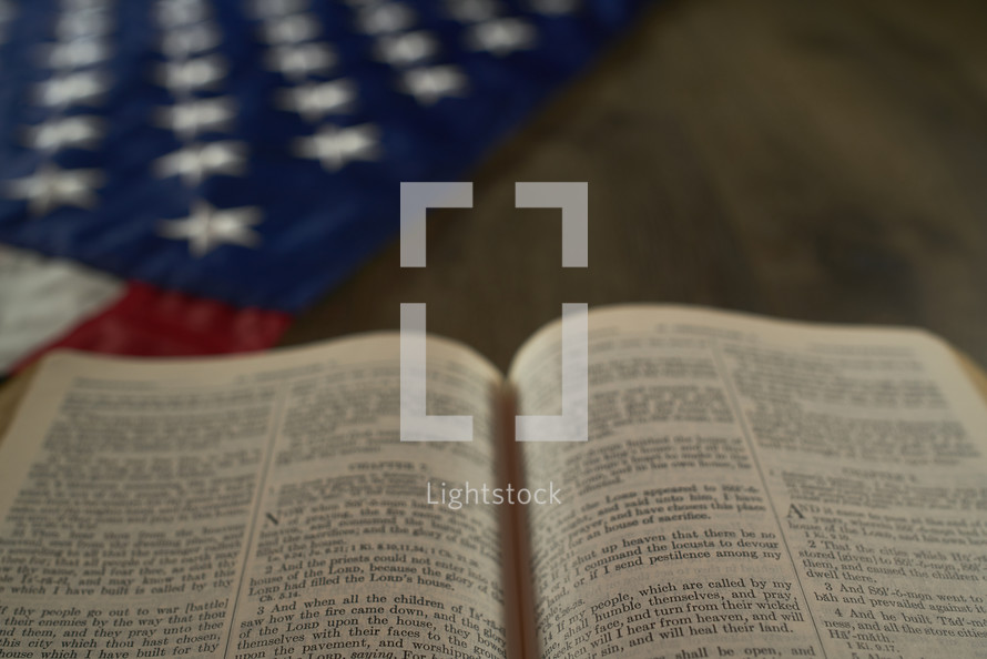 Open Bible next to the American flag