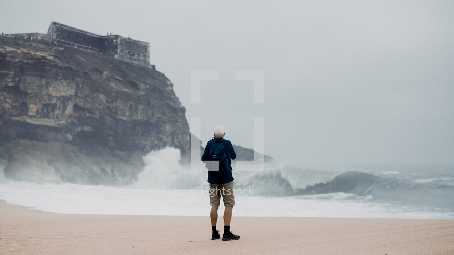 a man standing on a shore watching waves crash into rocks