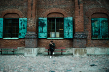 a man sitting on a bench in front of a warehouse taking a picture with a camera
