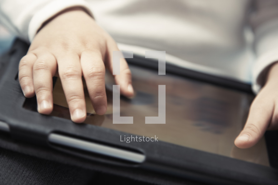 Hands of baby with digital tablet