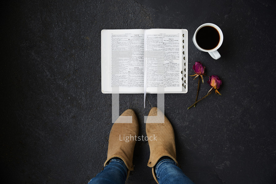 feet standing beside and open Bible, dried, roses, and coffee cup