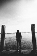 a man standing on a dock looking out at a harbor