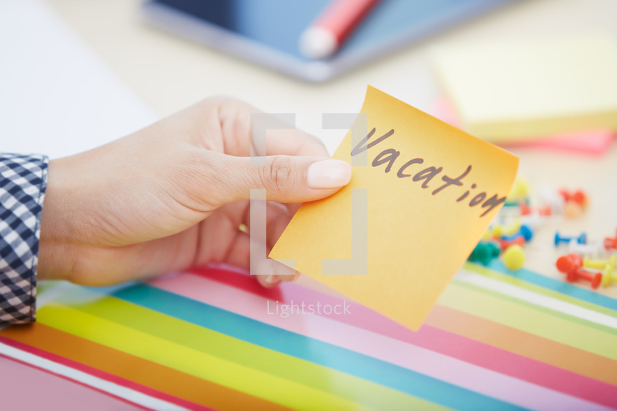 woman holding a sticky note with the word vacation on it