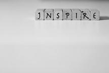 """Letter tiles spelling """"inspire."""