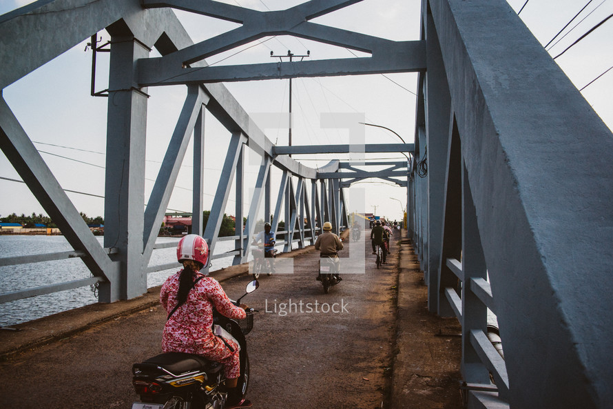 motorcycles crossing a bridge in Cambodia
