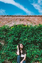 a young woman in front of a wall of ivy