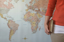world map and woman holding a Bible