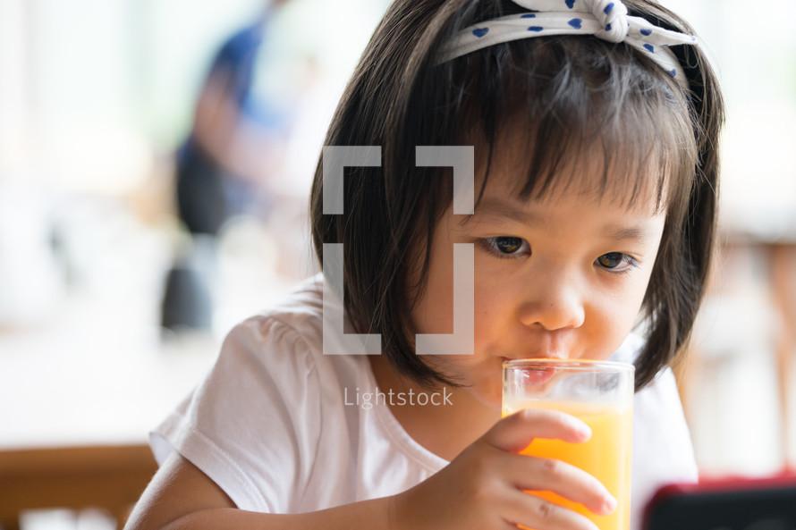 a little girl drinking orange juice