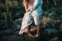 a couple standing on rocks embracing