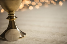 bokeh lights and chalice for communion