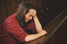 a woman sitting alone in a church pew with her hand on her forehead