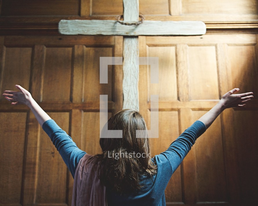a woman with hands raised standing in front of a cross