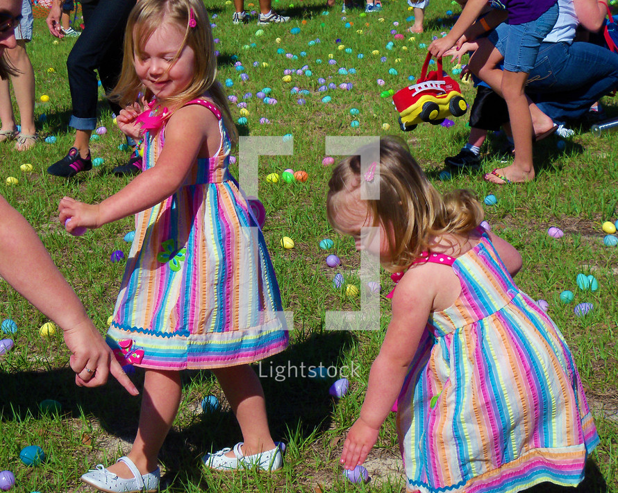 A set of twin girls with colorful dresses go Easter Egg hunting  along with other children in a green field of Easter eggs on Easter at a local church event.