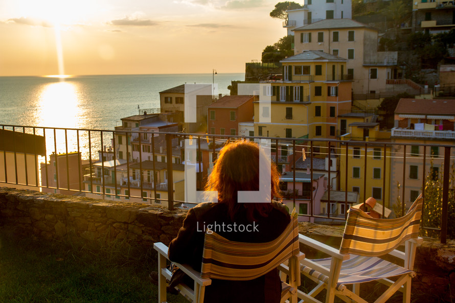 woman sitting watching the sunsetting over the ocean