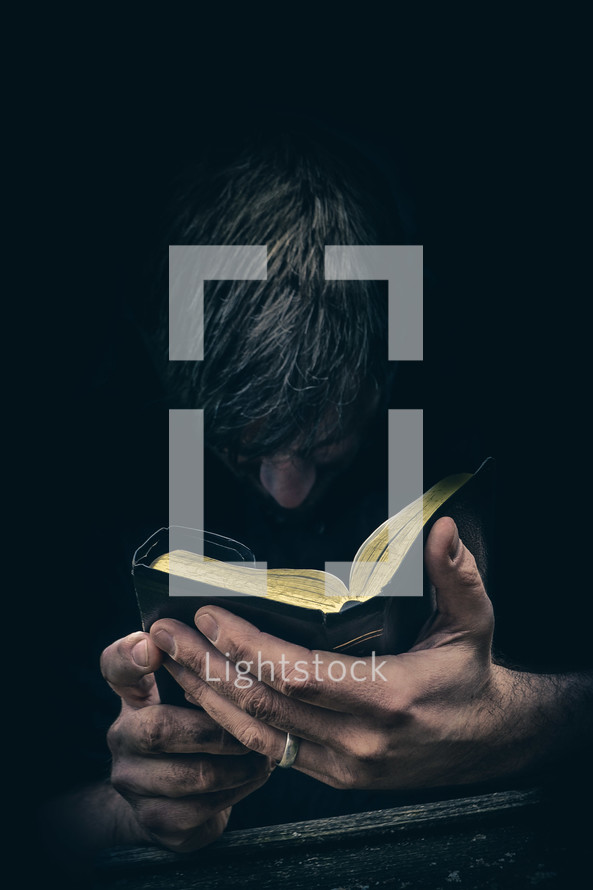 Man praying with head bowed before an open Bible held in both hands.