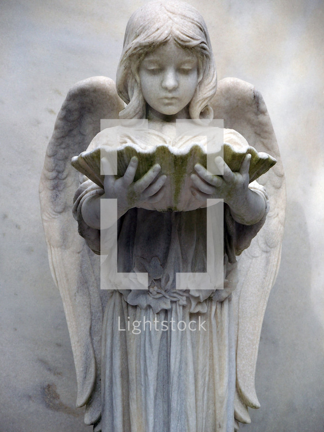 An Angelic female character statue holding an oyster shell in a historic cemetery in the southeastern United States as a grave marker and symbol of eternal rest among the Heavenly host of angels and God.