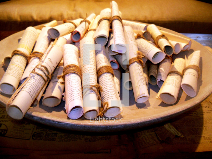 A bowl filled with old rolled up paper manuscript scrolls with the word of God and bible lessons printed to give out to people. In the early days, the word of God was written on parchments of scrolls of linen paper such as papyrus dating as far back as the early church. These scrolls are a reminder of how the word has endured the test of time and that the word of God is timeless enduring forever and a reminder that God's word will not return unto Him void but accomplish that which He pleases. Which is why we need to share the word of God as often as we can to tell people about Jesus.