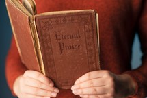 woman holding an old hymnal