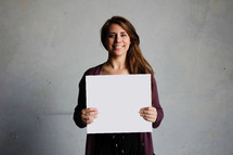 a woman holding a blank piece of paper