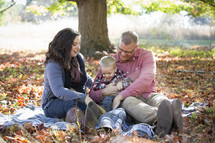 family sitting on a blanket in fall leaves