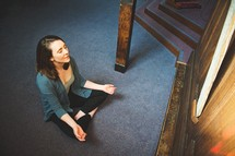 a woman sitting on the floor in prayer in a church