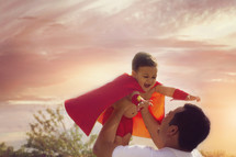 a father holding up his son in a cape