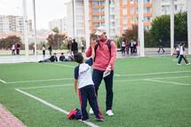 a boy giving a high five to his coach
