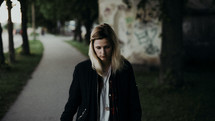 a young woman walking down a sidewalk