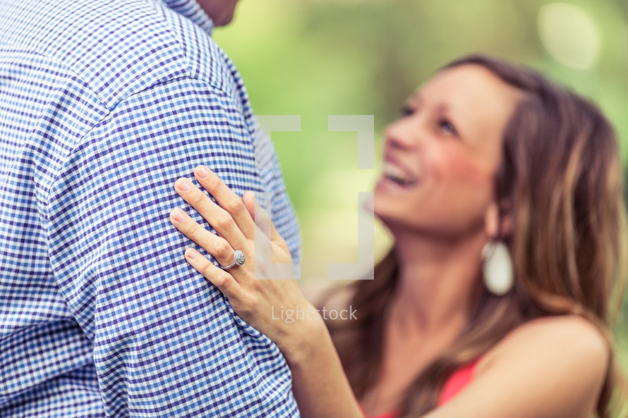 a woman with an engagement ring looking up at her fiancé