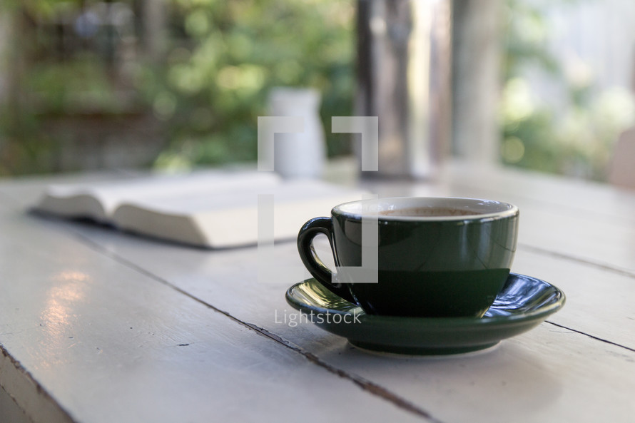 coffee cup and open Bible on a wood table