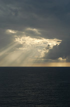 Sun beaming through clouds onto ocean