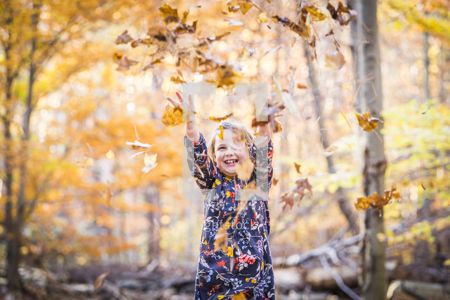 a little girl playing in fall leaves