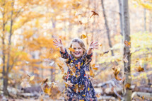 a girl child playing outdoors in fall