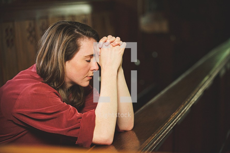 a woman praying alone in a church